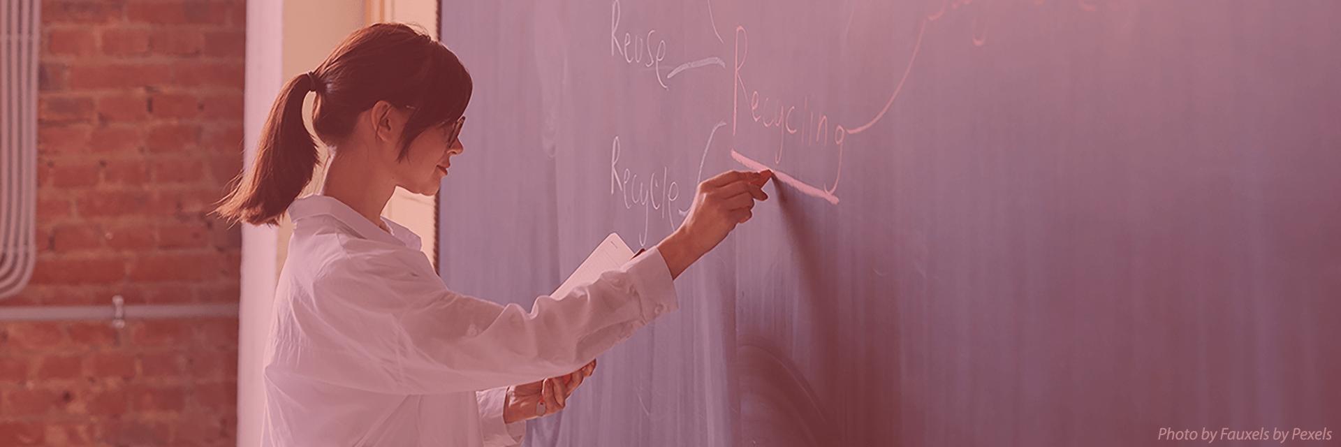 Female instructor writing on chalkboard